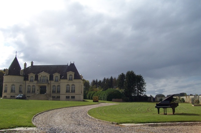 A storm rolling in, a black baby grand piano in front of a mansion. Just a typical French thing, oui?